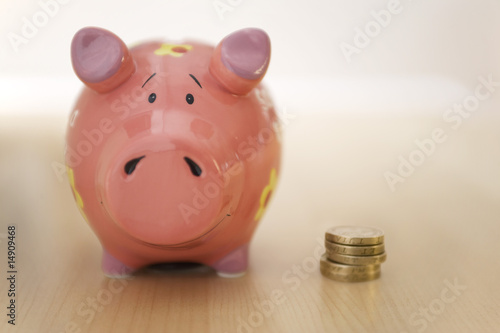 Stack of gold coins standing next to piggy bank
