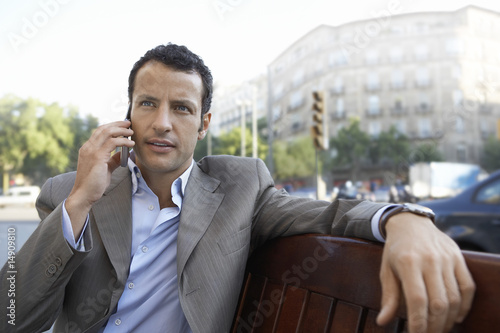 Businessman using mobile phone on city street