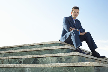 Young man wearing suit, sitting on marble staircase outdoors, portrait.