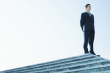 Businessman Standing on marble platform, low angle view.