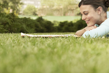 Woman lying on grass, reading newspaper, side view.