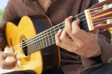 Man Playing classical guitar, mid section, close-up.