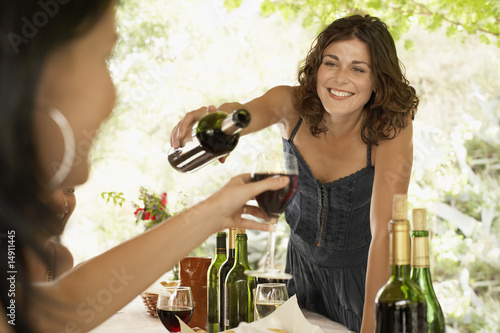 Two women at dinner party, one pouring wine for other.
