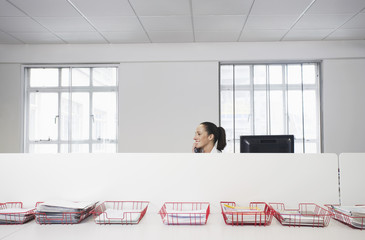 Female office worker using telephone, smiling, in office cubicle behind trays with documents