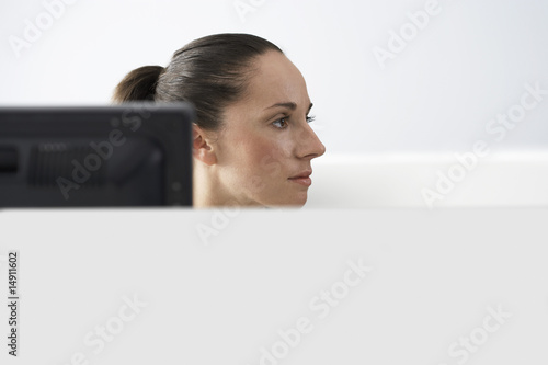 Female office worker sitting behind monitor in office cubicle, portrait