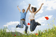 Young couple jumping for joy in mountain meadow, portrait, low angle view