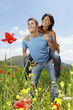 Young couple standing in mountain meadow, man giving woman piggy back, front view