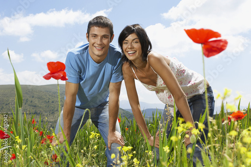 Young couple standing in mountain meadow, portrait, front view