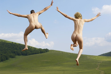Young naked couple running and jumping in mountain field, back view