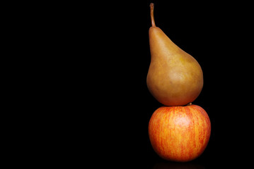 apple and pear on a black background