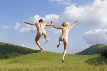 Young naked couple running and jumping in mountain field, back view, low angle view