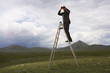 Businessman in mountain field on ladder Looking Through Binoculars, low angle view