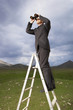 Businessman in mountain field on ladder Looking Through Binoculars