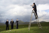 Businessman in mountain field Speaking Through Megaphone to other businessmen, full length