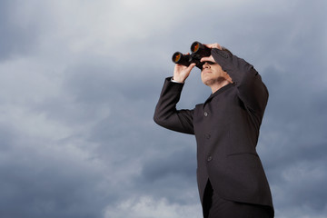 Low angle view of businessman looking through binoculars against stormy sky