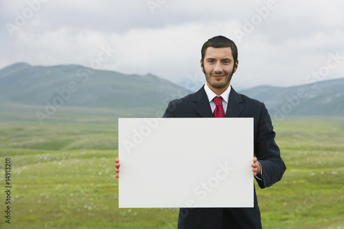 Smiling businessmen standing in mountain field holding blank sign, front view