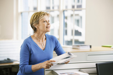 Middle-aged female office worker leaning on cubicle in office holding paperwork