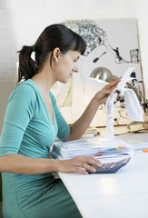 Businesswoman Examining Expenses with calculator
