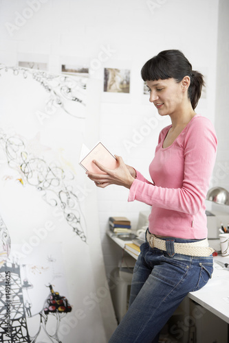 Businesswoman reading card leaning on desk