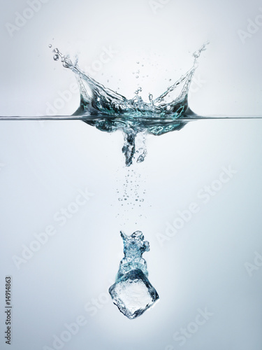 Ice cube splashing into clear water, surface view