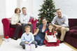 Family sitting by christmas tree in living room, portrait