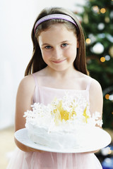 Girl holding Snowflake-Decorated Cake in living room
