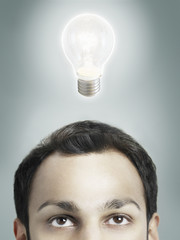 Illuminated lightbulb over man's head, high section, studio shot