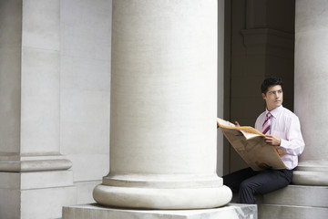 Businessman sitting on pillar under entablature reading newspaper