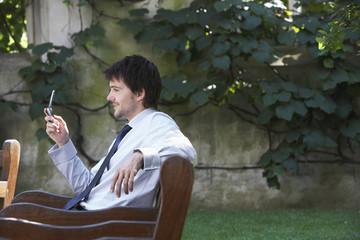 Businessman sitting on park bench sending text message