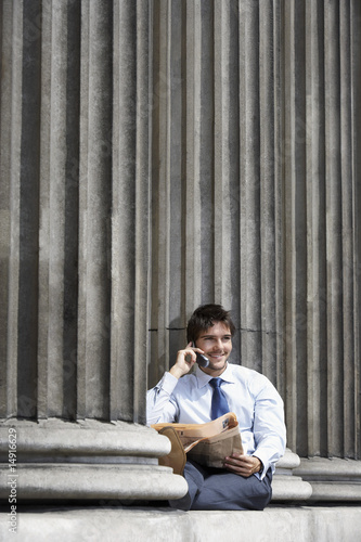 Businessman with newspaper sitting on pillar outside building talking on cell phone