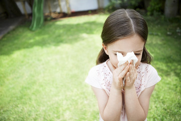 Little girl in backyard blowing nose, close up