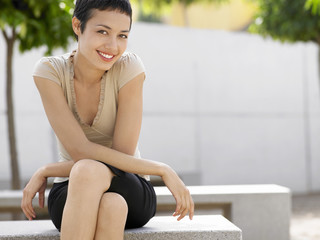 Smiling woman sitting on bench in plaza, portrait