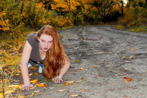 girl with red hair crawling in autumn forest