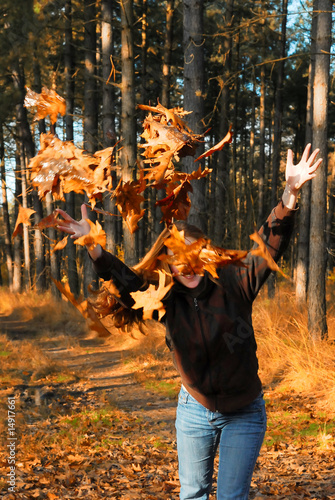 young girl throwing autumn leaves