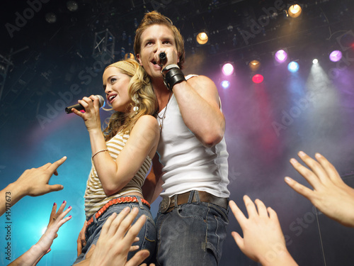 Young man and woman singing on stage in concert in front of adoring fans, low angle view