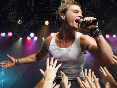 Young Man Singing on stage in concert close to adoring fans, low angle view