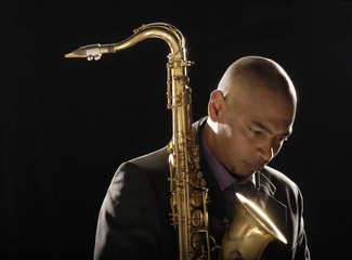 Pensive man holding saxophone, looking down, close-up