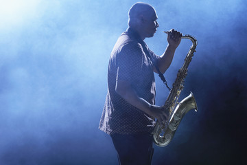 Man Playing Saxophone in smoky place, side view