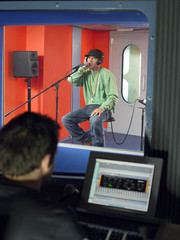 Young man singing in studio, technician in foreground