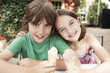 Two Kids Eating Ice Cream Cones at table in back yard, portrait