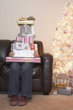 Person holding stack of Christmas gifts on sofa