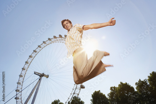 Young man in park jumping in front of London Eye, portrait, low angle view