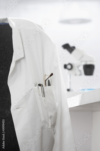 Scientists white coat in laboratory, with microscope in background