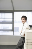 Businessman leaning against office photocopier, portrait