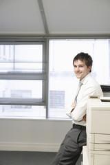 Businessman leaning against office photocopier, portrait
