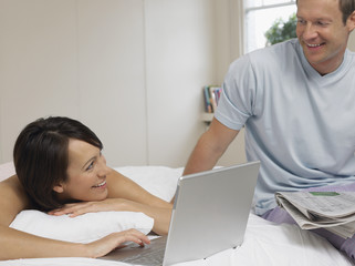 Woman with laptop on bed, man with newspaper