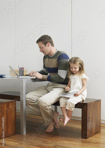 Father and daughter drawing and using laptop