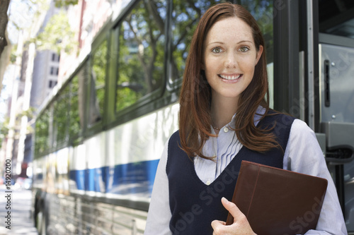 Young woman holding portfolio by bus, portrait