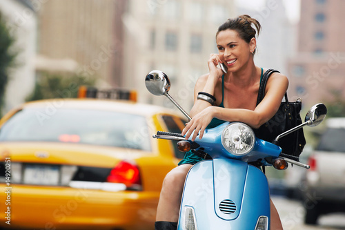 Woman using mobile phone on moped