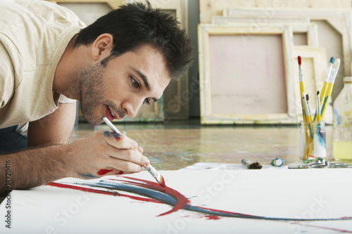 Man painting on canvas, on studio floor